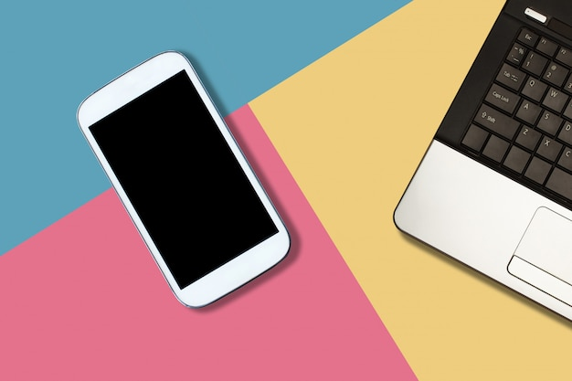 Smartphone with blank screen and laptop on pastel color background