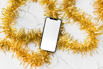 Smartphone with blank screen lying on tinsel