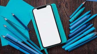 Смартфон с пустым экраном на дневник рядом синих цветов живописи и бумаги над деревянным столом