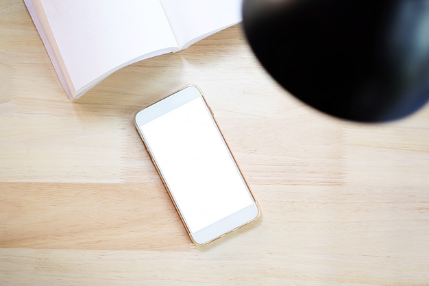 Smartphone with blank screen with book, lamp. flat lay style. top view.