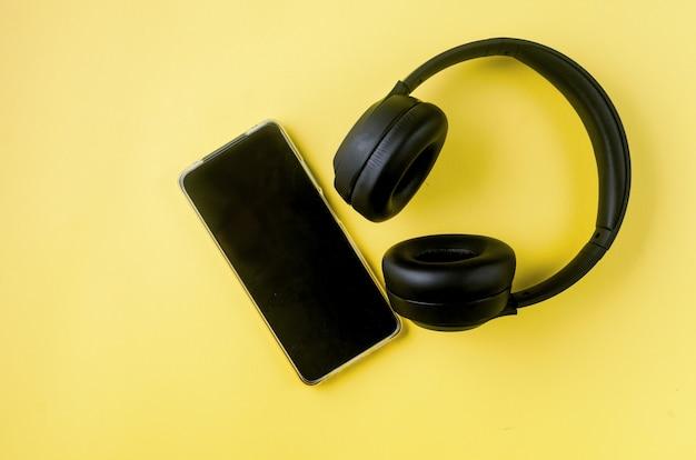 Смартфон с пустым экраном с наушниками на желтой бумаге