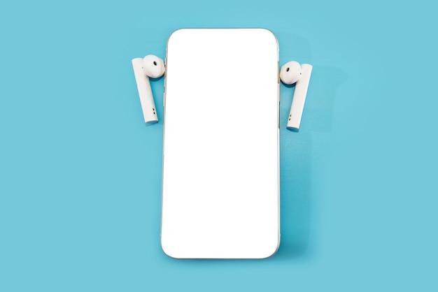 빈 흰색 화면 및 파란색 배경에 헤드폰 스마트 폰. 공간을 복사하십시오.