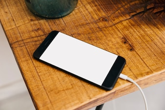 Smartphone with blank white screen on wooden desk