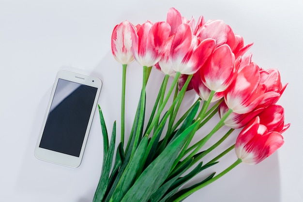ピンクのチューリップの花束を持つスマートフォン