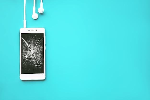 깨진 검은 화면과 헤드폰이 있는 스마트폰. 파스텔 시안색 배경에 평평하게 놓여 있습니다.