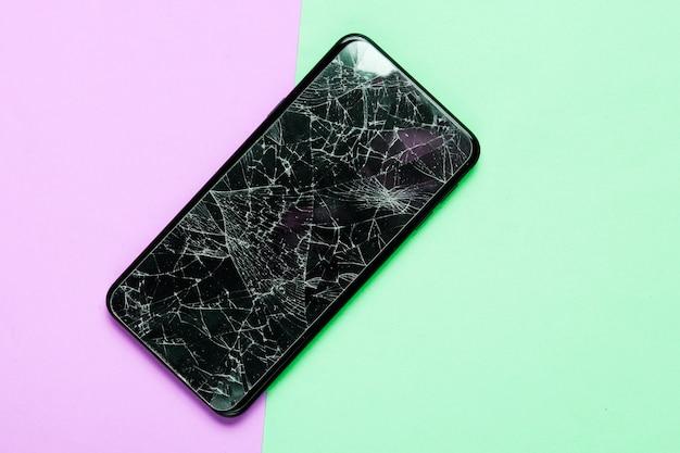 Смартфон с разбитым защитным стеклом на фоне paatel. вид сверху
