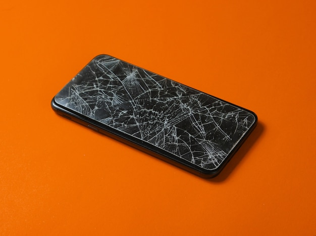 Smartphone with broken protective glass on orange background.