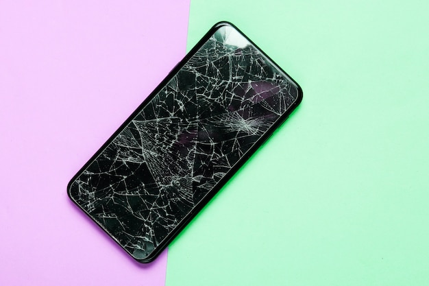 Smartphone with broken protective glass on paatel background. top view