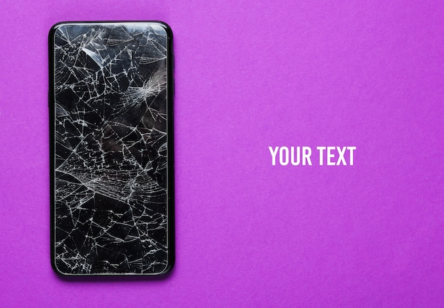 Smartphone with broken protective glass on purple background. top view. copy space
