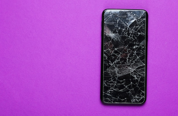 Smartphone with broken protective glass on purple table. top view