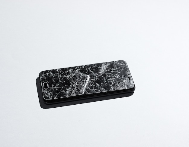 Smartphone with broken protective glass on white table.