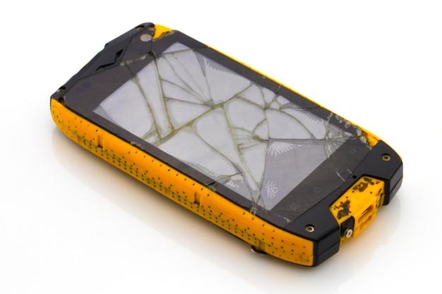白い背景で隔離の壊れた画面とスマートフォン