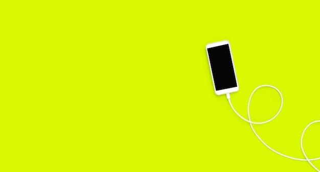 緑の表面に充電ケーブルを備えたスマートフォン