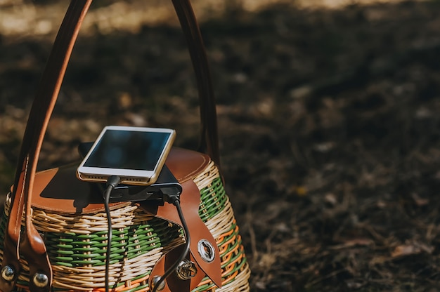 Smartphone with charging power bank on a basket in the forest. concept on the theme of outdoor recreation.