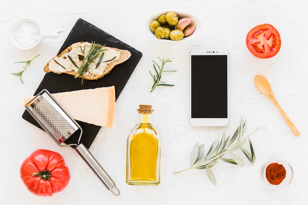 Smartphone with cheese, bread and ingredients on white backdrop
