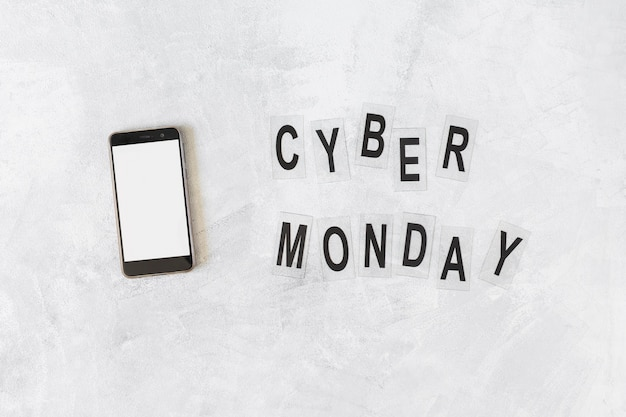 Smartphone with cyber monday inscription on table