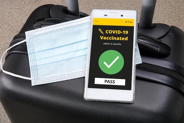 荷物にcovid-19のデジタル予防接種証明書が付いたスマートフォン。