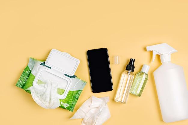 노란색 배경에 소독제 스프레이, 항균 물티슈, 손 소독제가 있는 스마트폰. 바이러스, 독감, 코로나바이러스, covid-19 보호용 개인 위생 제품