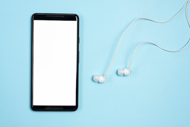 Smartphone with earphones on blue background