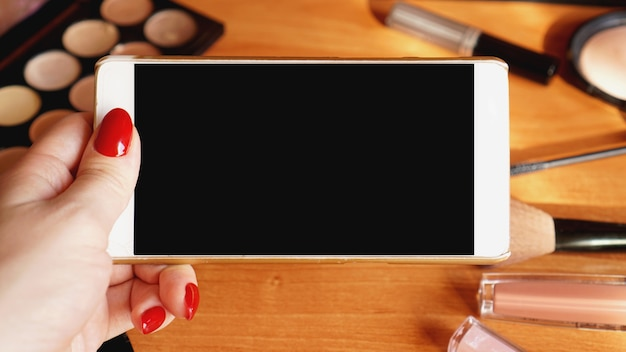 Smartphone with empty screen and cosmetics on light wooden background. top view, flat lay. mobile phone mockup.