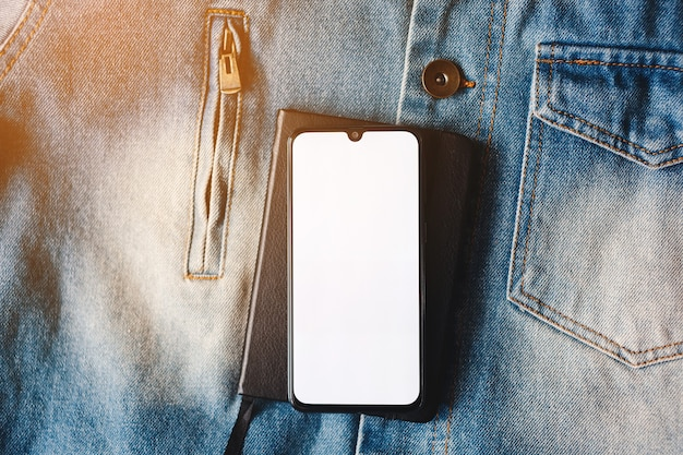 Smartphone with full screen display on the jeans background