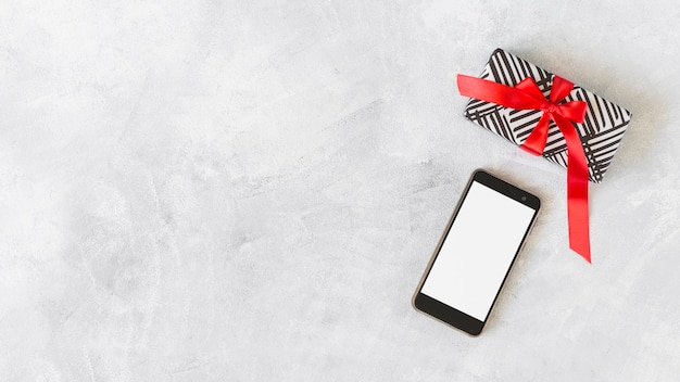 Smartphone with gift box on table