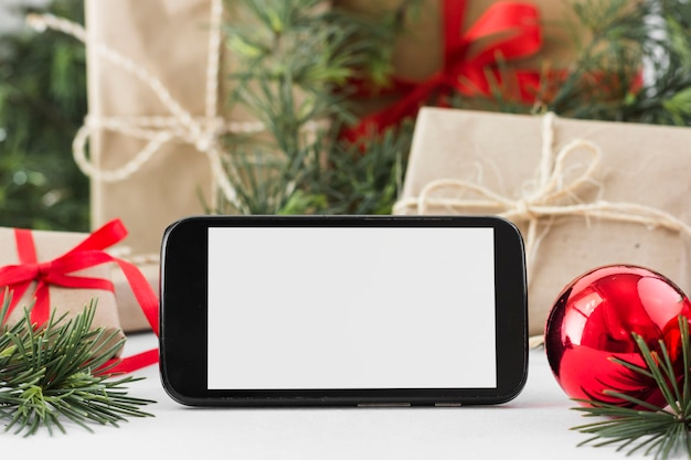 Smartphone with gift boxes on table