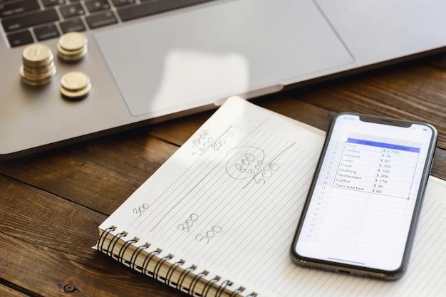 Смартфон со списком расходов на месяц на деревянном столе. планирование ежемесячной концепции домашнего финансирования