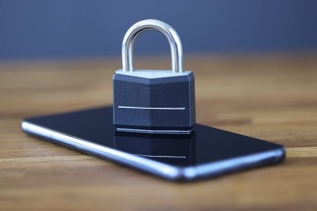 画面にロックがかかっているスマートフォンがテーブルの上にあります。インターネットペアレンタルコントロールの概念