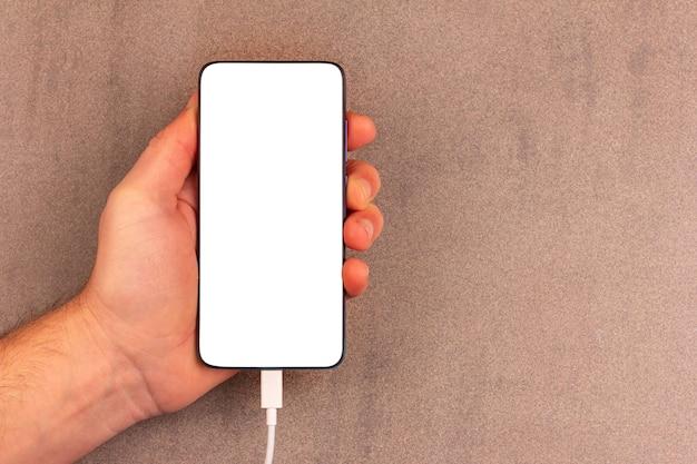 복사 공간이 있는 회색 갈색 배경에 남성 손에 모의 화면이 있는 스마트폰