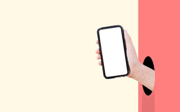パステルカラーの赤と黄色の2つの壁に穴からモックアップを手にしたスマートフォン。