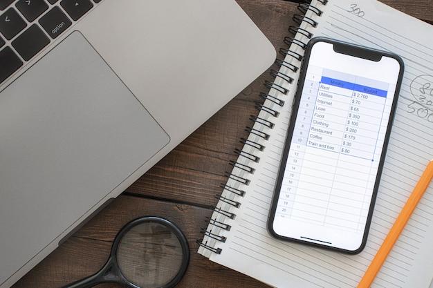 Смартфон с ежемесячным списком бюджета на деревянном столе. вид сверху концепции планирования домашнего бюджета. домашние финансы