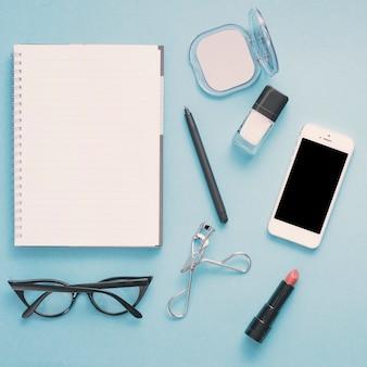 ノートブックと青いテーブルの上の化粧品のスマートフォン