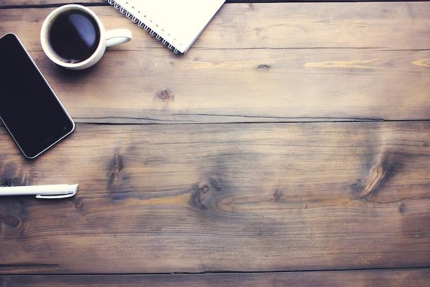 ノートブックと木製の背景にコーヒーのカップとスマートフォン