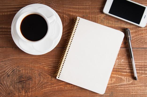 ノートブックと木製の背景にコーヒーのカップを持つスマートフォン。