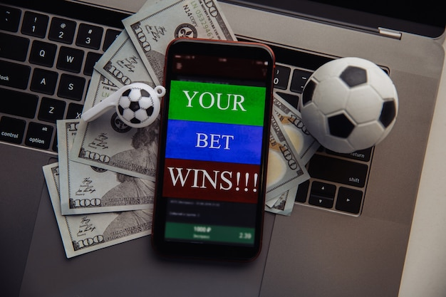 オンラインギャンブルアプリケーション、ドル札、キーボード上のサッカーボールを備えたスマートフォン。賭けの概念。上面図。