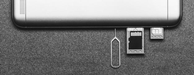 회색 배경에 sim 카드 및 마이크로 sd 메모리가있는 열린 슬롯이있는 스마트 폰