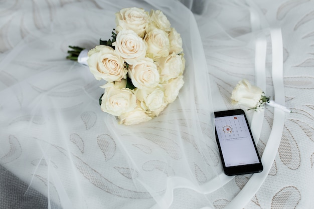 開いたカレンダー、結婚式のボタンホール、ベールに白いバラのウェディングブーケを持つスマートフォン