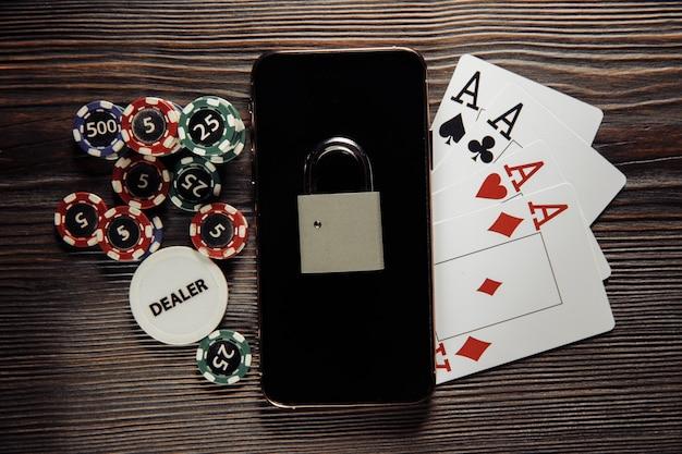 Смартфон с замком, фишками для покера и игральными картами. понятие закона и регулирования азартных игр