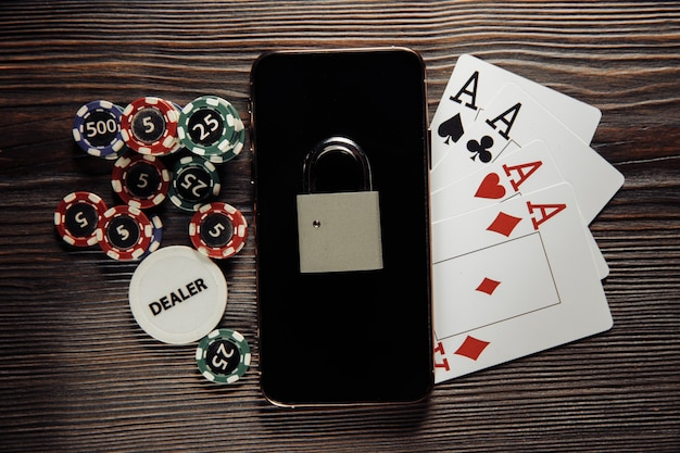 Smartphone with padlock, poker chips and playing cards. concept of law and regulation of gambling