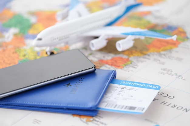 Smartphone with passport and tickets and an airplane lie on geographic map searching for