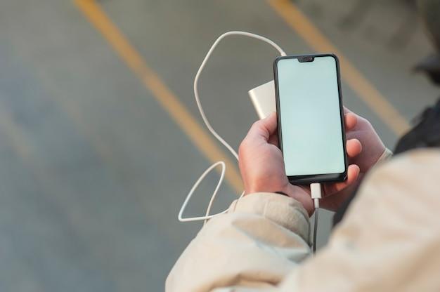 Смартфон с портативной зарядкой в руках человека.