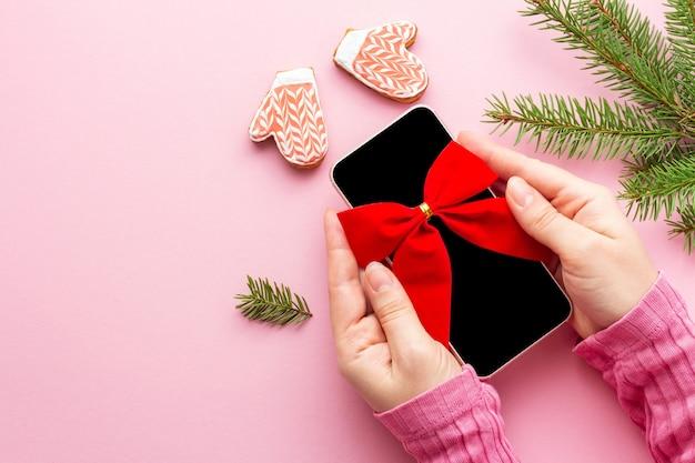 Смартфон с красным бантом в женских руках под углом, как рождественский подарок на розовом фоне