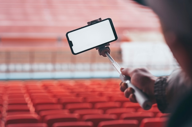 Smartphone with a selfie stick in the hands