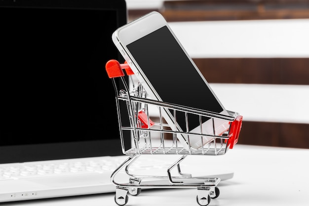 Smartphone with shopping cart on white