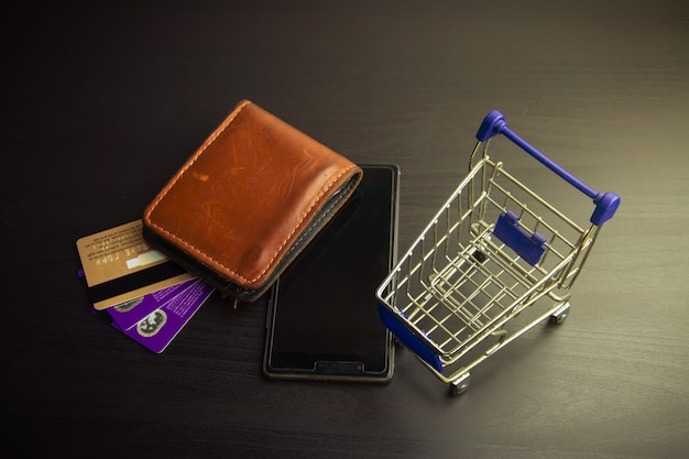 Smartphone with shopping cart on wood