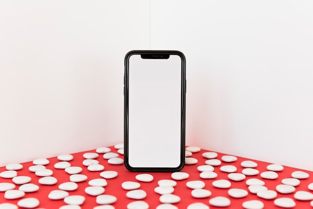 Smartphone with small hearts on table