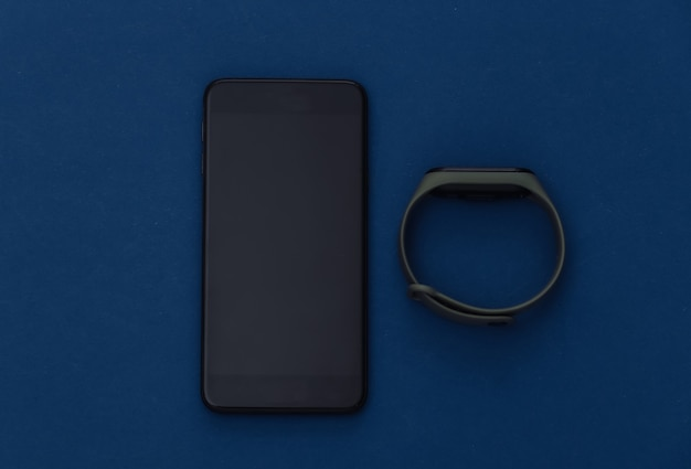 Smartphone with smart bracelet on a classic blue background. modern gadgets. color 2020. top view.