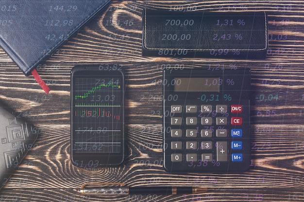 株価グラフ、ノートブック、木製の机の上のノートパソコンのキーボードを持つスマートフォン。取引の概念