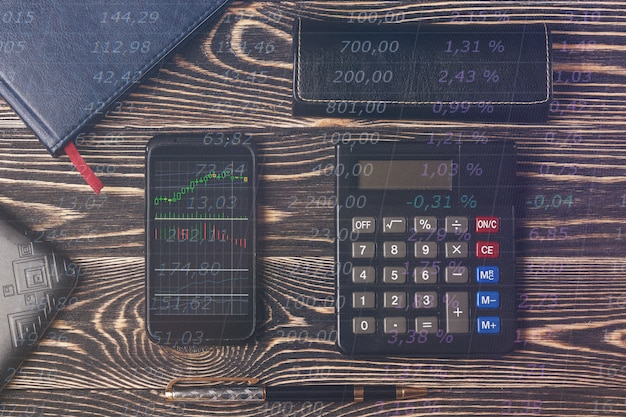 Smartphone with stock graph, notebook, laptop keyboard on wooden desk. trading concept.